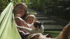 Happy mother and daughter relaxing together in a hammock at garden in summer day stock footage