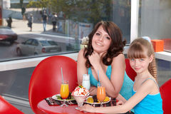 Happy mother and daughter in restaurant. Royalty Free Stock Image