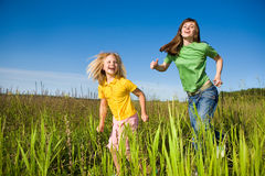 Happy mother and daughter run on field. Against the backdrop of blue sky Stock Photo