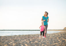 Happy mother and daughter running on beach at sunset Stock Photo