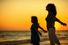 Happy mother and daughter on seacoast at sunset rejoicing stock photo