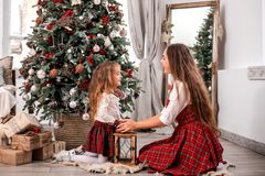Happy mother and daughter seating near fir-tree. stock image