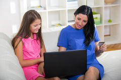 Happy mother and daughter shopping online Stock Photography