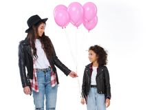 Happy mother and daughter in similar clothes with pink balloons. Isolated on white royalty free stock images