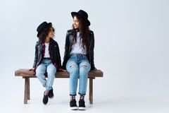 Happy mother and daughter in similar clothes sitting on bench together. Isolated on grey stock photography