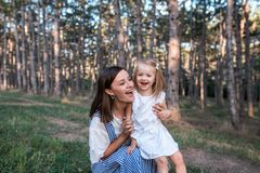 Happy mother and daughter singing together outdoors. stock image