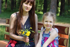 Happy mother and daughter sit with flowers Royalty Free Stock Images