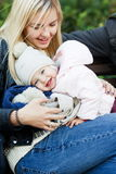 Happy mother with daughter sitting on bench in autumn park Stock Image