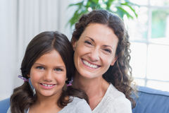 Happy mother and daughter sitting on the couch and smiling at camera Stock Images