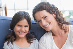 Happy mother and daughter sitting on the couch and smiling at camera Stock Photography
