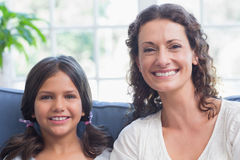 Happy mother and daughter sitting on the couch and smiling at camera Royalty Free Stock Photos