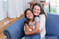Happy mother and daughter sitting on the couch and smiling at camera Stock Photo