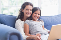 Happy mother and daughter sitting on the couch and using laptop Royalty Free Stock Photography
