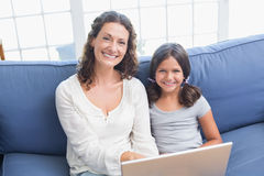 Happy mother and daughter sitting on the couch and using laptop Royalty Free Stock Image