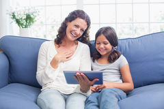 Happy mother and daughter sitting on the couch and using tablet Stock Photos