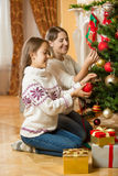 Happy mother and daughter sitting on floor at living room and de Stock Image