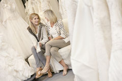 Happy mother and daughter sitting with footwear on sofa in bridal store Stock Photography