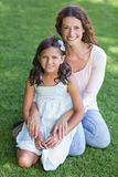 Happy mother and daughter sitting on the grass Stock Image