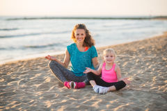 Happy mother and daughter sitting in lotus position on beach Stock Photography