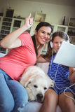 Happy mother and daughter sitting with pet dog and using digital Stock Images