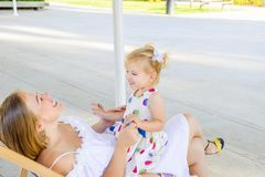 Happy mother and daughter sitting, relaxing in the deckchair in the city park recreation area and having fun togetther. Family rec stock image