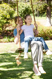 Happy mother and daughter sitting on swing at park Royalty Free Stock Photography