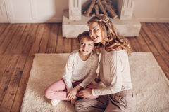Happy mother and daughter sitting together on carpet and looking away Royalty Free Stock Images