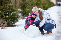 Happy mother with daughter sitting together in snow at winter park Royalty Free Stock Photo