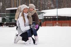 Happy mother and daughter skating on a outdoor skating rink royalty free stock image