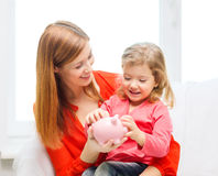 Happy mother and daughter with small piggy bank Stock Photos