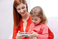 Happy mother and daughter with smartphone at home Royalty Free Stock Images