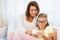 Happy mother and daughter with smartphone at home royalty free stock photography