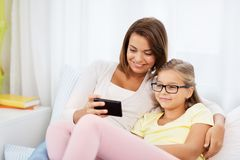 Happy mother and daughter with smartphone at home stock image