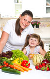 Happy mother and daughter smiling in the kitchen Stock Image