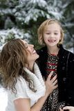 Happy Mother and Daughter in the Snow. A cute young girl missing her front tooth with a happy smile.  Her Mom is holding on tight with an equally beaming smile Royalty Free Stock Photos