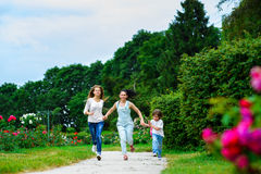 Happy Mother with daughter and son running on Royalty Free Stock Images