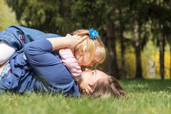 Happy mother and daughter in spring park. Young women and little girl playing in spring park. Happy mother and daughter Royalty Free Stock Images