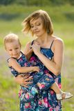 Happy mother and daughter standing in field. Outdoor shot Royalty Free Stock Images