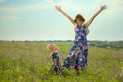 Happy mother and daughter standing in field. Outdoor shot Royalty Free Stock Photos