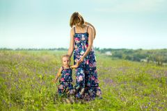 Happy mother and daughter standing in field. Outdoor shot Stock Images
