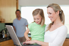 Happy mother and daughter surfing the web with father in the bac Stock Photo