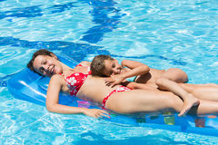 Happy mother and daughter swimming in the pool Stock Images