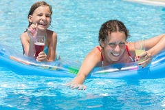 Happy mother and daughter swimming in pool Royalty Free Stock Images