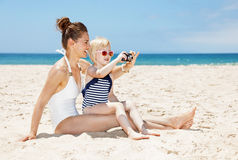 Happy mother and daughter in swimsuits taking photos at beach Stock Photos