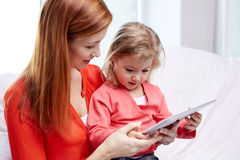 Happy mother and daughter with tablet pc computer Royalty Free Stock Images