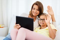 Happy mother and daughter with tablet pc at home royalty free stock photos