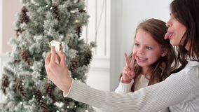 Happy mother and daughter taking funny Christmas selfies at home stock video footage