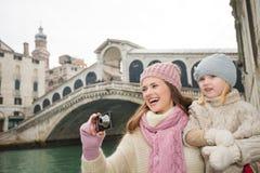 Happy mother and daughter taking photos near Rialto Bridge Stock Photo