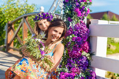 Happy mother and daughter under the arch for the wedding ceremony. Floristic composition in vintage style. The Provence. stock image