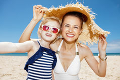 Happy mother and daughter under big straw hat taking selfie Stock Photos
